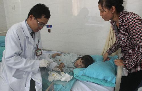 Bác sĩ hướng dẫn mẹ Minh Anh cách rửa vết thương, chăm sóc bàn tay bé khi xuất viện về nhà. Ảnh: Lê Phương.