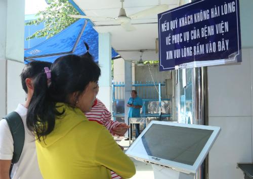Phụ huynh dùng máy để phản ánh chất lượng dịch vụ khi đưa con đến khám bệnh tại Bệnh viện Nhi đồng 1 sáng 31/1. Ảnh: T.P