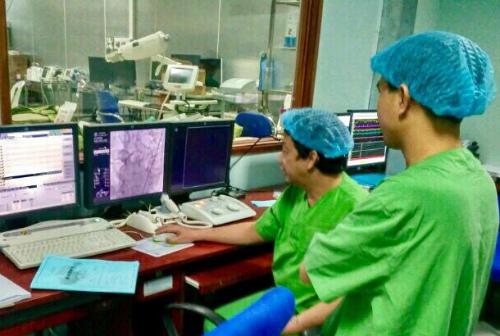 Phó giáo sư Hồ Thượng Dũng và bác sĩ Phan Văn Trực hội chẩn can thiệp mạch vành cấp cứu bệnh nhân nhồi máu cơ tim biến chứng ngưng tim ngưng thở từ Bệnh viện Đa khoa Trung tâm An Giang. Ảnh: M.T
