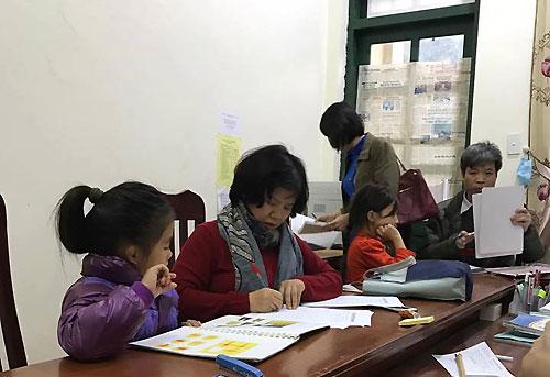 Các bác sĩ Bệnh viện Nhi Trung ương làm bài test tâm lý cho các học sinh tại điểm trường có 9 trẻ bị chứng rối loạn phân ly tập thể. Ảnh: Bác sĩ cung cấp.