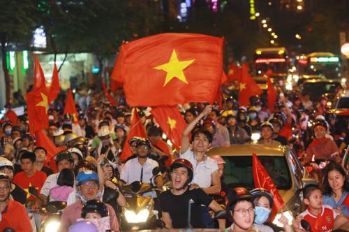 Người dân TP HCM đổ ra đường ăn mừng chiến thắng của đội tuyển U23 Việt Nam tối 23/1. Ảnh: Thành Nguyễn.