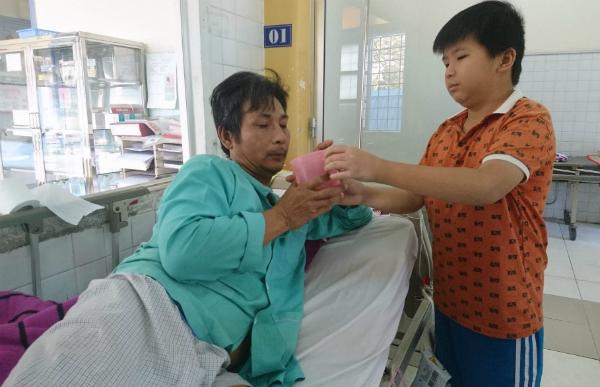 Con trai anh Đông chăm bố trong viện. Ảnh: L.P