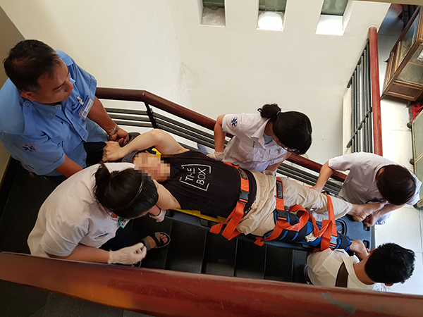 Các y bác sĩ cùng tài xế xe cấp cứu khiêng bệnh nhân xuống 3 tầng lầu để đi viện sau khi sơ cứu ban đầu tai nạn gãy chân. Ảnh: Lê Phương.