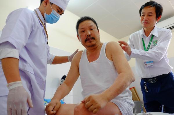 Anh Đông (ở giữa) sau 5 năm bị liệt có thể ngồi dậy cạnh bác sĩ Trần Văn Khanh (bên phải). Ảnh: Lê Phương.