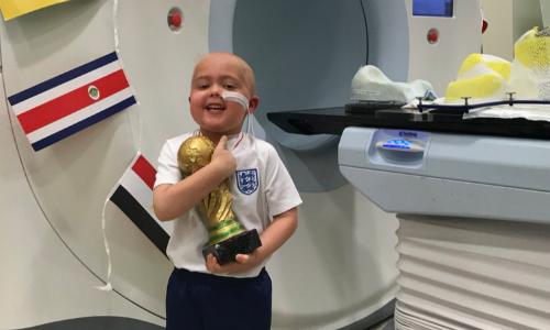 Bé Ben ôm cúp vàng sau khi hoàn thành sáu tuần xạ trị. Ảnh: Twitter.