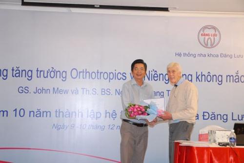 Thạc sĩ, bác sĩ Nguyễn Quang Tiến tặng hoa cám ơn Giáo sư John Mew chuyển giao công nghệ Niềng răng tăng trưởng cho Nha khoa Đăng Lưu.