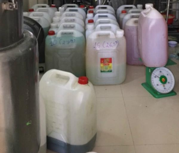 Nguyên liệu được đựng trong các can nhựa không nhãn mác đặt dưới nền nhà. Ảnh: Ban Quản lý An toàn thực phẩm TP HCM.
