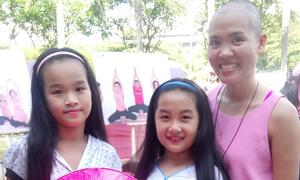 Hai bé gái cắt mái tóc dài tặng bệnh nhân ung thư