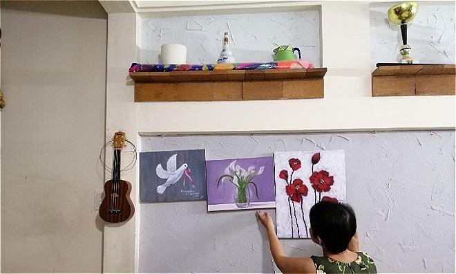 Mai và những bức tranh cô tự vẽ tại nhà riêng. Bức tranh đầu tiên từ trái sang sẽ được cô tặng cho Thủy Tiên như một món quà cảm ơn. Mai đã là thành viên của mạng lưới BCNV được ba năm. Ảnh: Sen