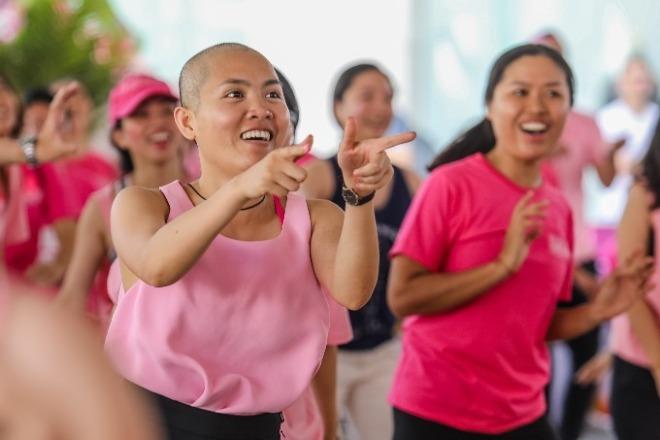 Nguyễn Thủy Tiên, Giám đốc điều hành và nhà đồng sáng lập của Mạng Lưới Ung Thư Vú Việt Nam hòa mình vào điệu nhảy với thành viên mạng lưới và tình nguyện viên của mình tại Ngày Hội Nón Hồng. Ảnh: Thành Nguyễn