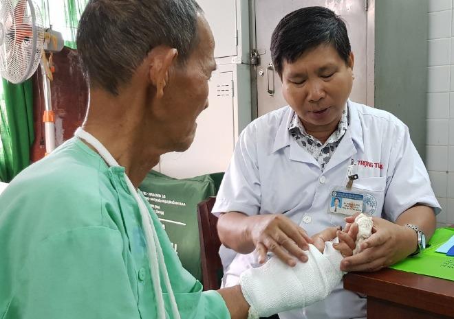 Bác sĩ Tường kiểm tra cử động tay của bệnh nhân. Ảnh: Lê Phương.