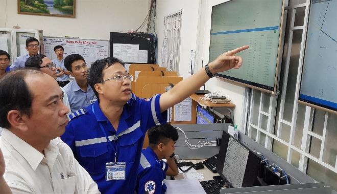 Bác sĩ Nguyễn Duy Long, Giám đốc Trung tâm Cấp cứu TP HCM (áo xanh) giải thích về hệ điều hành thông minh cho phó giám đốc Sở Y tế TP HCM. Ảnh: Lê Phương.