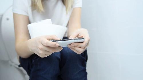 Mang điện thoại vào nhà vệ sinh giống như đi ra mà không rửa tay. Ảnh: BZ.