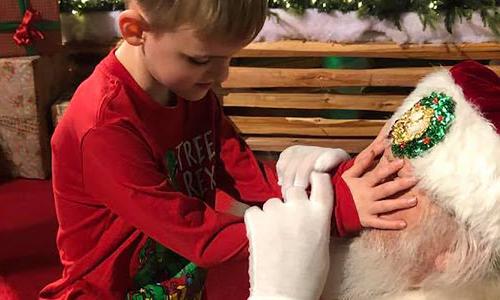 Matthew chạm vào mắt Ông già Noel để cảm nhận đôi mắt lấp lánh. Ảnh: FN.
