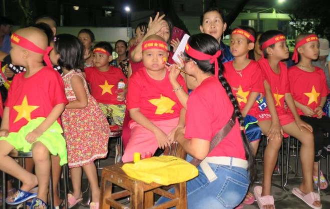 Các bệnh nhi ung thư mặc áo thun đỏ, vẽ cờ lên mặt cổ vũ trận chung kết lượt đi AFF Cup tối 11/12. Ảnh: P.L