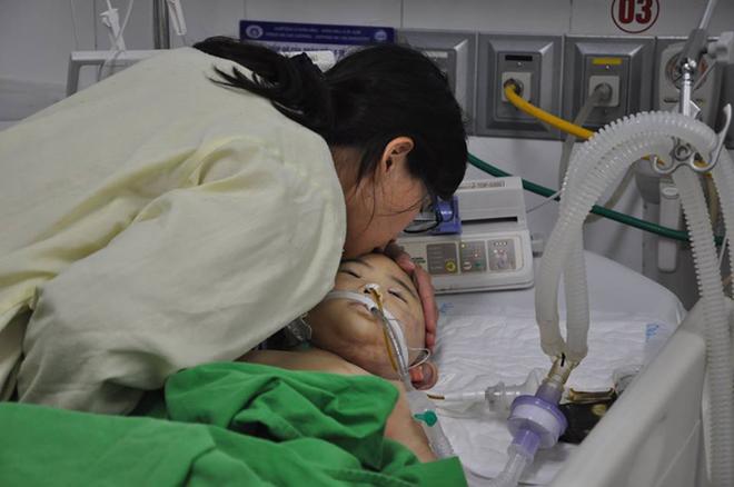 Nụ hôn tiễn biệt của người mẹ trước khibác sĩ nhận giác mạc của bé Mai Reon. Ảnh: Hoàng Nguyễn.