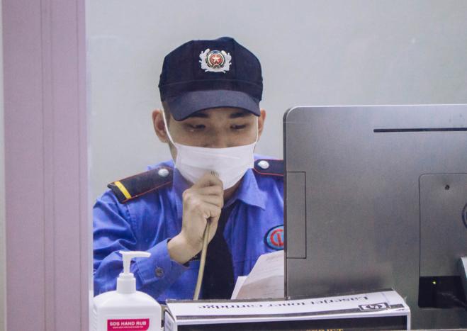 Thuận tập trung, đọc bộ đàm gọi người nhà bệnh nhân tại phòng tiếp đón. Ảnh: Thùy An