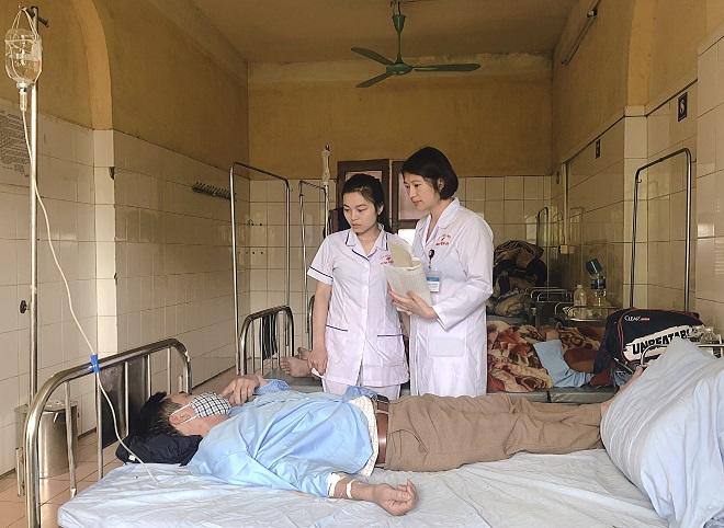 Chị Thúy cùng điều dưỡng đi buồng, thăm hỏi bệnh nhân. Ảnh: Thùy An