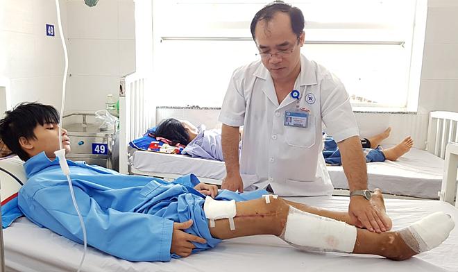 Tiến sĩ Võ Thành Toàn kiểm tra chức năng chân bệnh nhân ngày 7/3. Ảnh: Lê Phương.