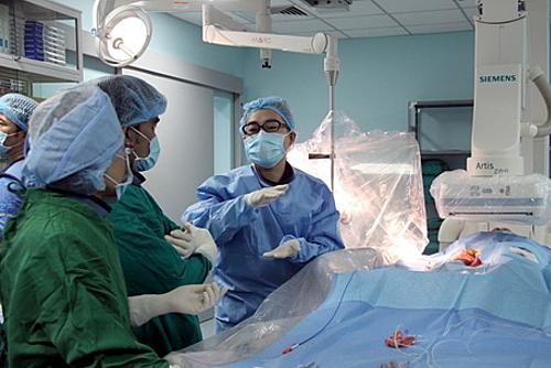 Chuyên gia Nhật Bản về tim mạch can thiệp (phải) trao đổi kinh nghiệm với các bác sĩ Bệnh viện đa khoa Đồng Nai trong một ca bệnh. Ảnh: Phước Tuấn