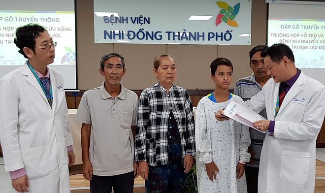 Tiến sĩ Trương Quang Định trao sổ tiết kiệm cho gia đình bé trước khi xuất viện. Ảnh: Lê Phương.
