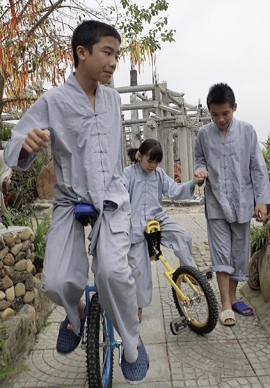 Tùng Dương ngồi xe đạp 1 bánh đỡ bé gái khác tập luyện cùng. Ảnh: Thùy An
