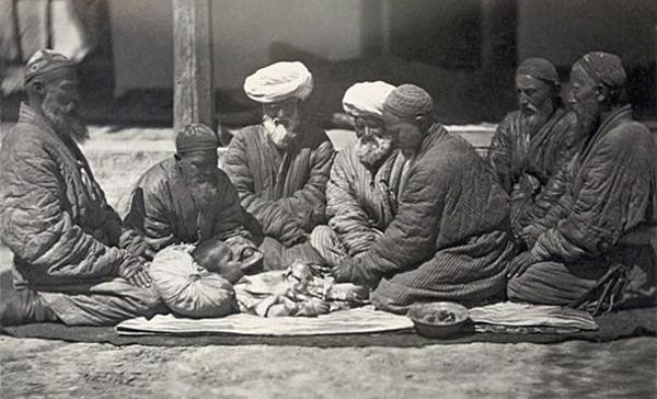 Cảnh một nhóm người đàn ông ngồi trên mặt đất gần một cậu bé đang bị cắt bao quy đầu.