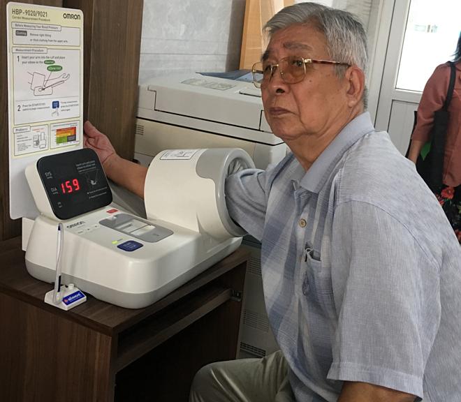 Người lớn tuổi được đo huyết áp trước khi khám bệnh. Ảnh: Cẩm Anh