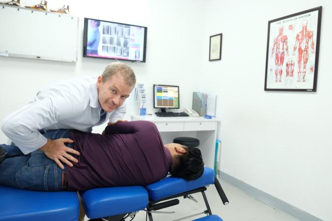 Bác sĩ Timothy Gallivan đang nắn chỉnh cột sống lưng cho bệnh nhân thoát vị đĩa đệm bằng phương pháp Trị liệu thần kinh cột sống Chiropractic.