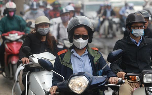Người đi xe máy đeo khẩu trang tránh bụi trên đường Minh Khai. Ảnh: Tất Định.