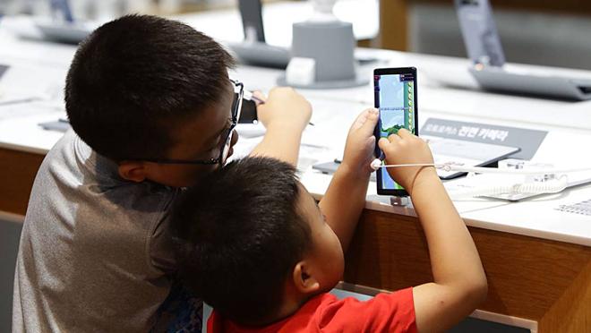 Sử dụng các thiết bị điện tử thông minh như điện thoại, máy tính là một trong những nguyên nhân chính khiến trẻ em lười vận động. Ảnh: Vnexpress