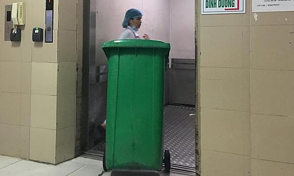 Nhân viên y tế vận chuyển thùng chứa rác thông thường tại Bệnh viện Nhiệt đới Trung ương. Ảnh: Lê Nga.
