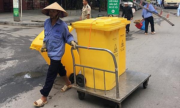 Nhân viên vận chuyển thùng đựng chất chât nguy hại lây nhiễm tại bệnh viện. Ảnh: Lê Nga.