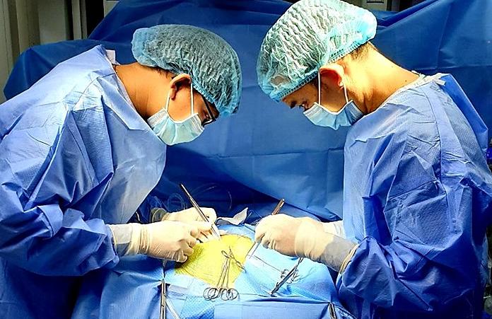 Các bác sĩ đang can thiệp mạch máu li ti của bé trai để chuẩn bị tiến hành chạy ECMO. Ảnh bệnh viện cung cấp.