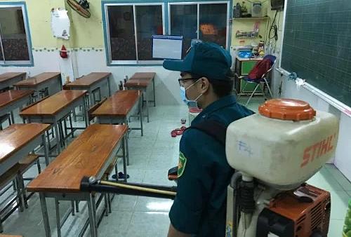 Nhân viên y tế dự phòng quận 5, TP HCM phun thuốc diệt muỗi ở một trường tiểu học. Ảnh: Hoài Nhơn