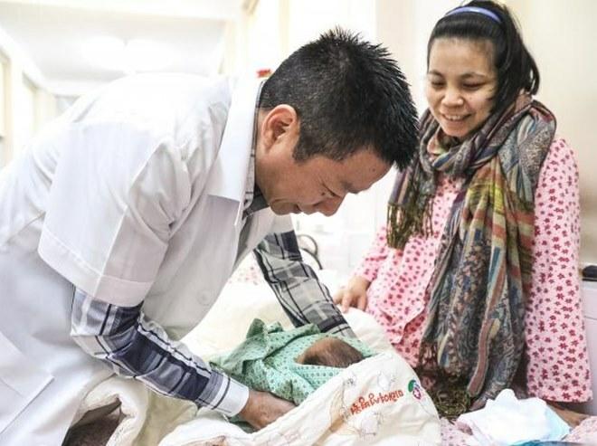 Bác sĩ Khải với một bé sơ sinh tại Bệnh viện Phụ sản Hà Nội. Ảnh: NVCC