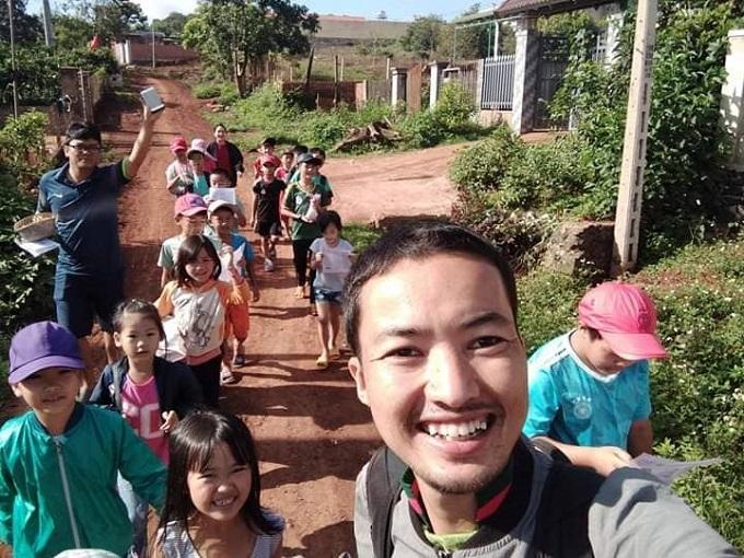 Thầy giáo 9X cùng các em nhỏ tham gia một giờ học thực hành ngoài trời.