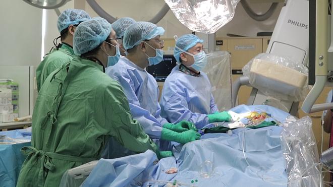 Các bác sĩ thực hiện thủ thuật thay van động mạch chủ qua da cho người bệnh. Ảnh do bệnh viện cung cấp