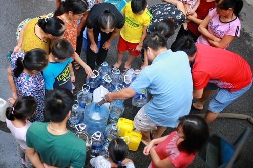 Người dân Hà Nội xếp hàng lấy nước sạch từ xe tec. Ảnh: Giang Huy.
