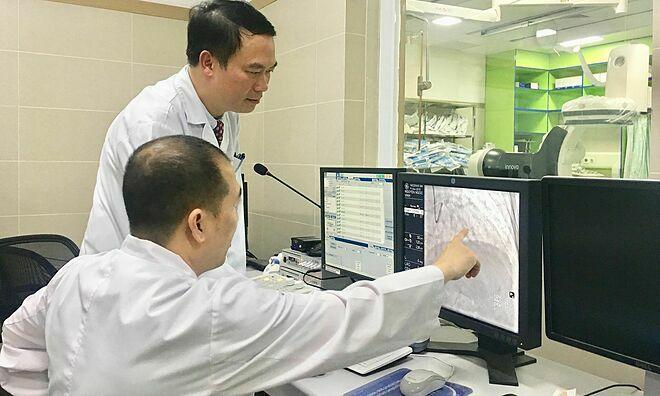 Phó giáo sư Hùng cùng đồng nghiệp chẩn đoánca bệnhtim mạch. Ảnh: Lê Nga.