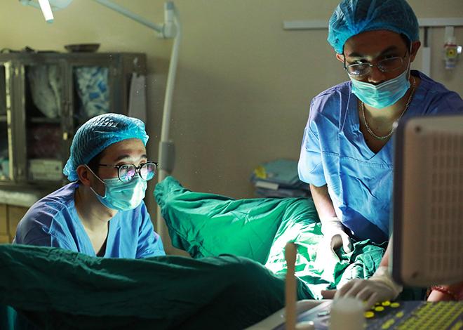 Bác sĩ Hà ( trái) và đồng nghiệp đang tiến hành chuyển phôi cho bệnh nhân. Ảnh: Bệnh viện cung cấp