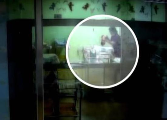 Hình ảnh từ camera ghi lại cảnh nữ y tá dốc ngược đầu em bé xuống cũi. Ảnh: Korea Times