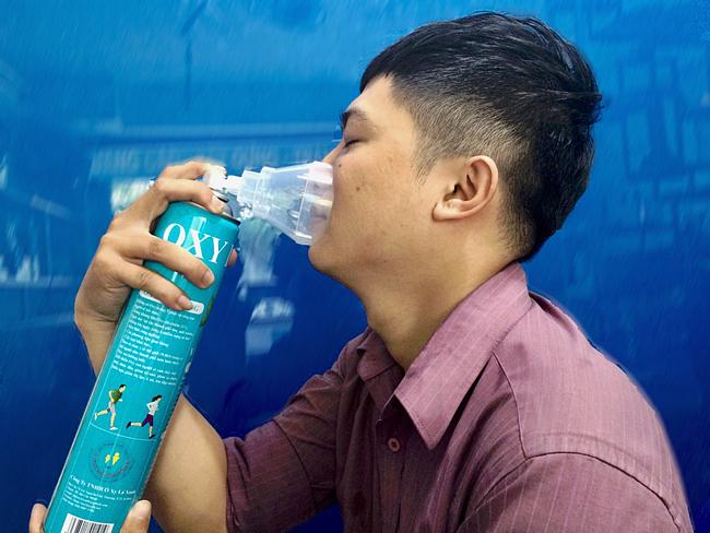 Bình oxy được gắn mặt nạ ở đầu ống van, khi người dùng ấn nút van, oxy sẽ xả ra ngoài. Ảnh: Cẩm Anh
