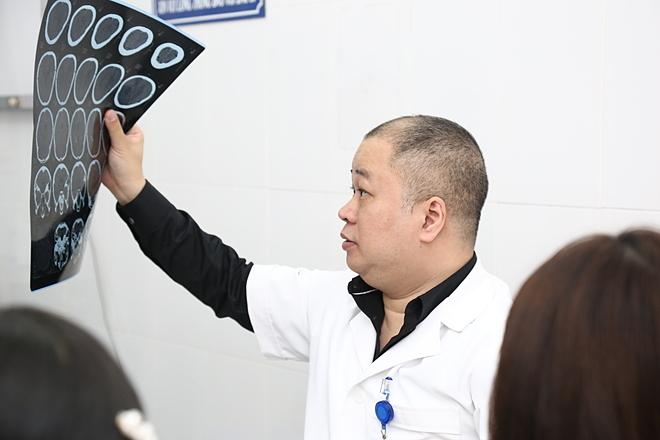 Bác sĩ Tuấn đọc phim chụp cho bệnh nhân tai biến mạch máu não. Ảnh: Hương Nguyễn.