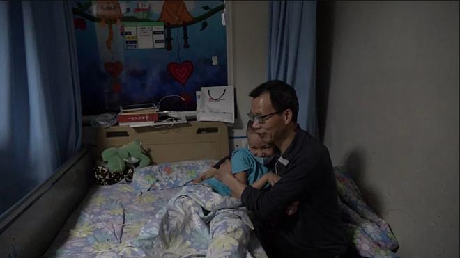 Liu Wei bế con trai Liu Xuntao trong phòng bệnh ung thư tại Bệnh viện Nhân dân tỉnh Tứ Xuyên. Ảnh: SCMP