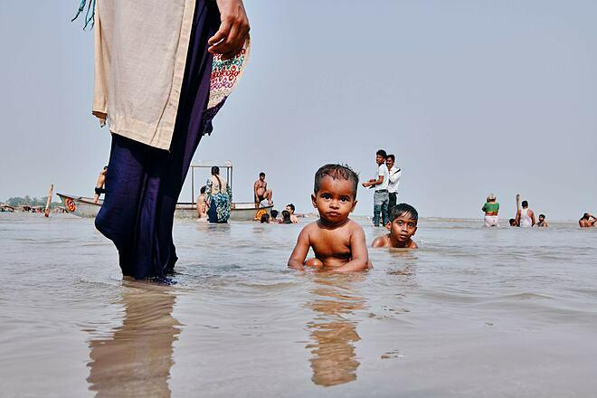 Bé trai Ấn Độtắm tại sông Hằng dù ôn nhiễm. Ảnh: New York Times