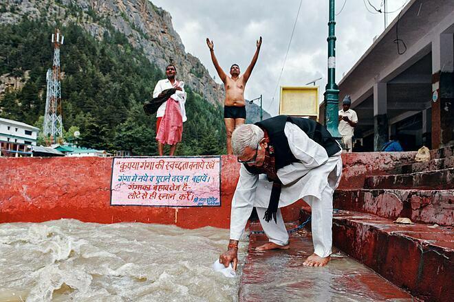Một người hành hương múc nước ở sông Hằng. Ảnh: New York Times