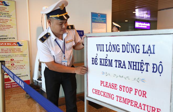 Nhân viên Trung tâm Kiểm dịch y tế quốc tế điều chỉnh bảng thông báo kiểm tra thân nhiệt khách nhập cảnh tại sân bay quốc tế Cam Ranh. Ảnh: Xuân Ngọc.