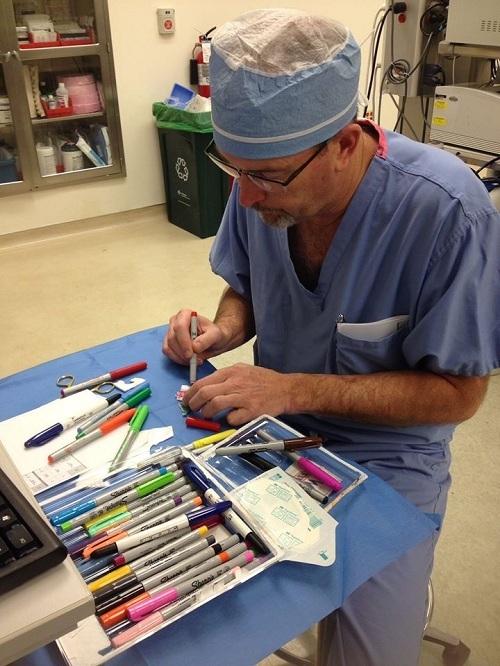 Bác sĩ Robert Parry vẽ hình lên miếng dán y tế cho các bệnh nhi. Ảnh: Akron Childrens Hospital