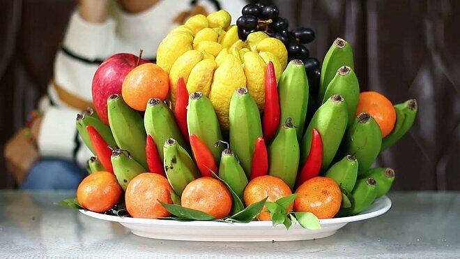Mâmngũ quả ngày Tết của người miền Bắcvớinải chuối đặt ở dưới cùng đỡ lấy toàn bộ loại quả khác.